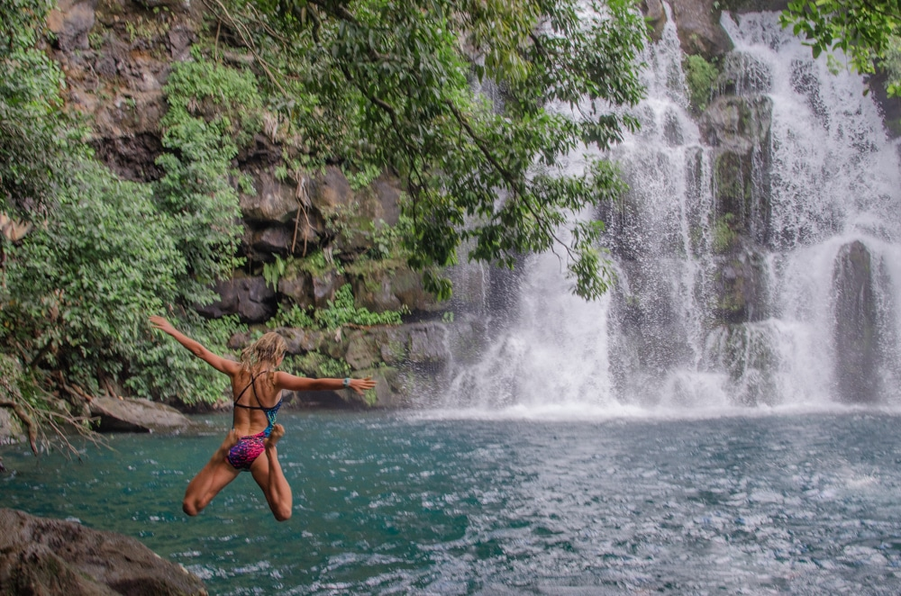 Girls jumps into mauritius waterfall pool